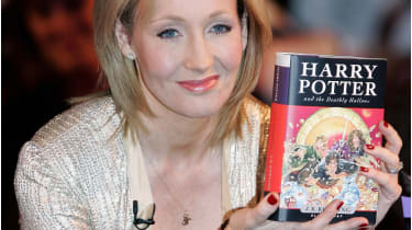 """.K. Rowling holds a copy of """"Harry Potter and the Deathly Hallows"""" SHAUN CURRY/AFP via Getty Images"""