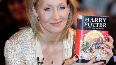 ".K. Rowling holds a copy of ""Harry Potter and the Deathly Hallows"" SHAUN CURRY/AFP via Getty Images"