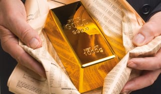 Hands holding a gold bar wrapped in the FT