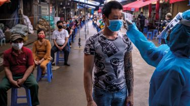 Health worker taking market trader's temperature in Vietnam © Linh Pham/Getty Images