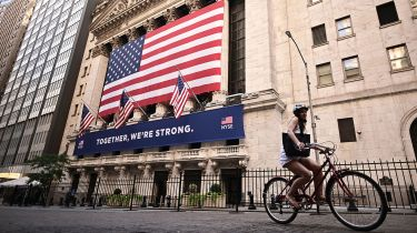 Woman riding a bike past the New York Stock Exchange