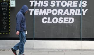 A man walks past a closed shop