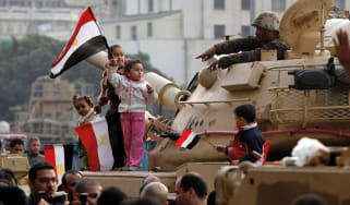 Kids standing on a tank in Tahrir Square, waving Egyptian flags