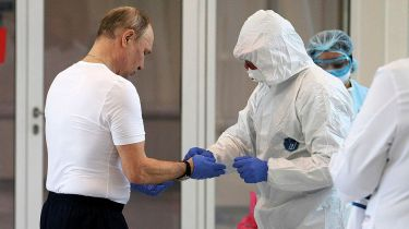 President Vladimir Putin putting on a personal protective suit ©