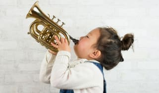 Small girl playing a trumpet ©
