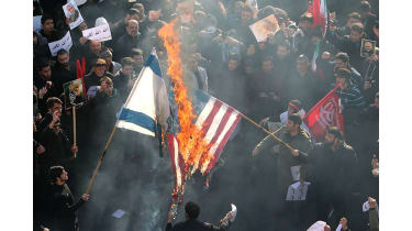 US and an Israeli flags on fire © ATTA KENARE/AFP via Getty Images