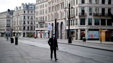 Pedestrian wearing a face mask on a deserted street © TOLGA AKMEN/AFP via Getty Images