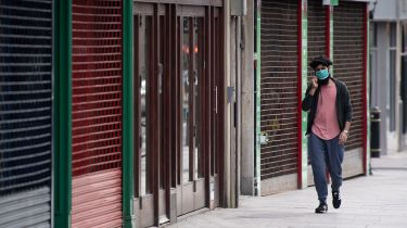 Man walking by a row of closed shops ©