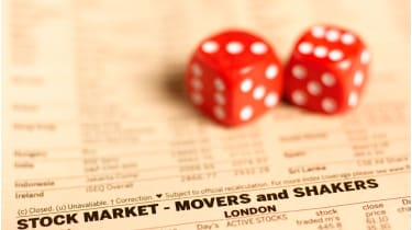 Pair of dice on financial pages © Getty Images