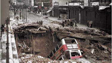 A bus in a large crater in the road ©