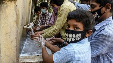 Indian children with facemasks wash their hands © NOAH SEELAM/AFP via Getty Images