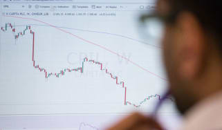 Trader looking at a chart © Chris Ratcliffe/Bloomberg via Getty Images