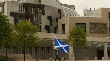 Man waving a flag in front of the Scottish Parliament. © Jeff J Mitchell/Getty Images