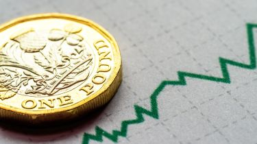UK pound coin next to a financial growth chart