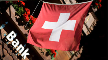 Swiss flag and bank © FABRICE COFFRINI/AFP via Getty Images