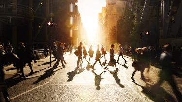 People crossing the street with the sun rising in the background