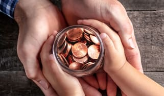 Adult's and child's hands round a jar of coins