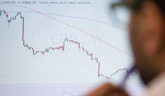 Trader looking at a financial chart © Chris Ratcliffe/Bloomberg via Getty Images