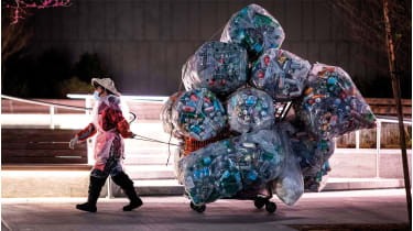 A woman pulling a trolley loaded with bags of recyclables © JOHANNES EISELE/AFP via Getty Images