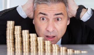 Man looking at a shrinking pile of coins