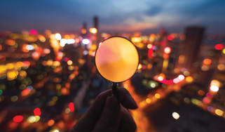 A magnifying glass examines a city