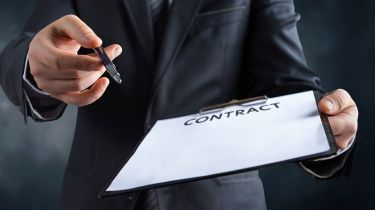 Hands holding a pen and blank contract