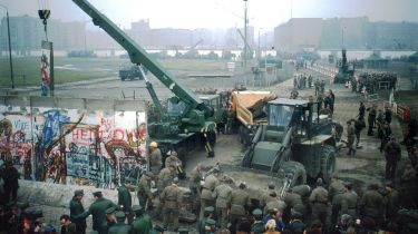 East Germans dismantling the Berlin Wall