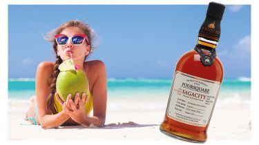 Woman drinking a cocktail, and a bottle of rum © Getty Images/iStockphoto
