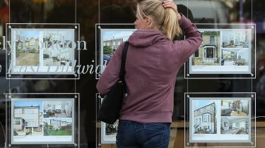 Woman looking in an estate agent's window