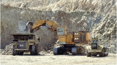 Excavator filling a dump truck at a gold mine