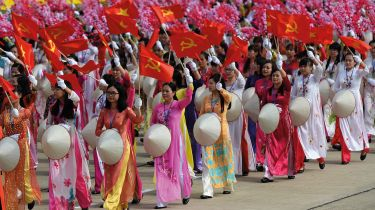 """Women in traditional """"ao dai"""" dress parading in Vietnam © HOANG DINH NAM/AFP via Getty Images"""