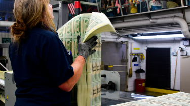 US mint worker holding sheets of $20 bills © AFP via Getty Images