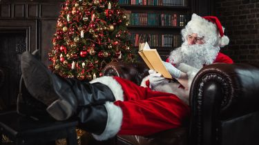 Father Christmas with his feet up reading a book