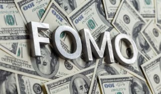 FOMO letters sitting on top of US dollars