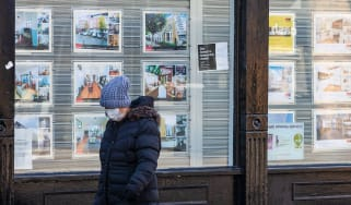 A pedestrian with a face mask passes a closed estate agent ©