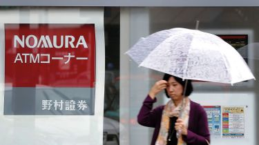 Pedestrian walking past a Nomura bank branch