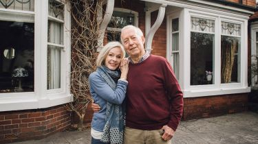 Old couple in front of a house © Getty